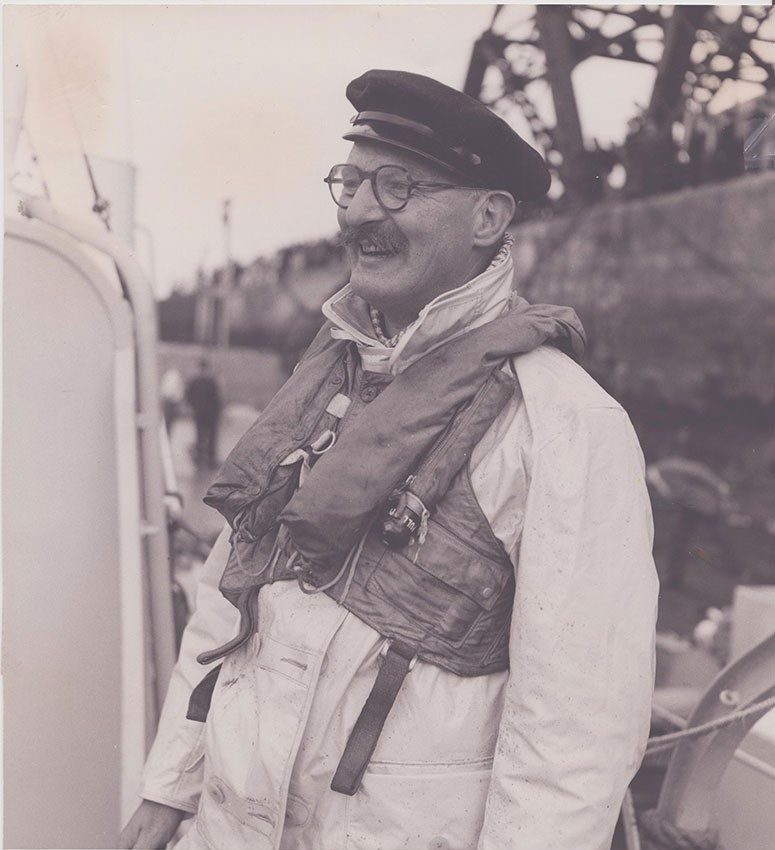 Sir Christopher Cockerell wearing a lifejacket and hat, smiling on a boat.