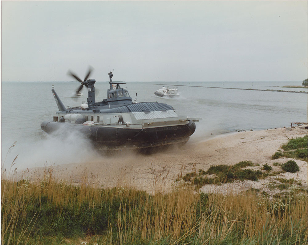 A BH7 Hovercraft exiting the sea onto a stone beach